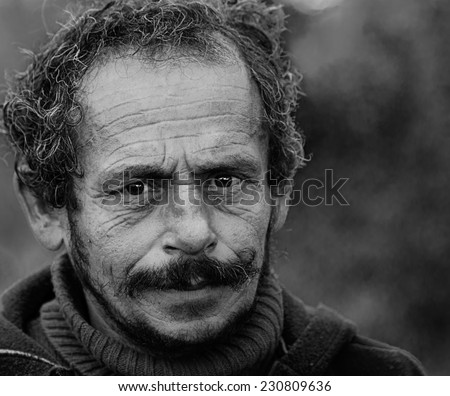 Portrait of a bearded homeless man.Face emotions