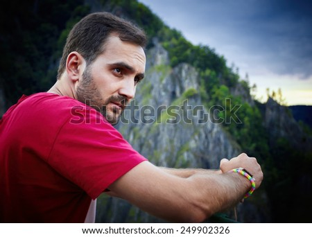 Portrait of a bearded man, wearing a red shirt and hands resting on a railing between the mountains. - stock photo