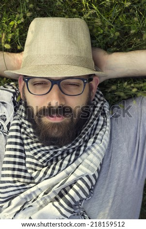 Portrait of a bearded smiling young hipster man lying in the grass and daydreaming - stock photo