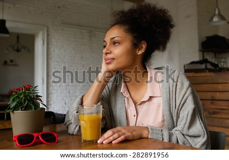 Portrait of a beautiful african american woman sitting at home thinking - stock photo