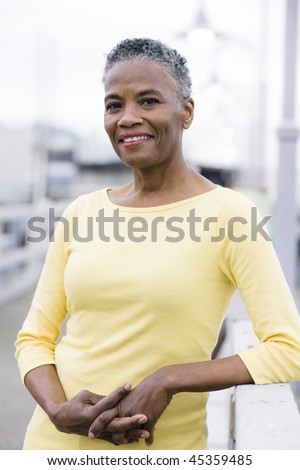 Portrait of a Beautiful African American Woman Standing on a Wharf - stock photo