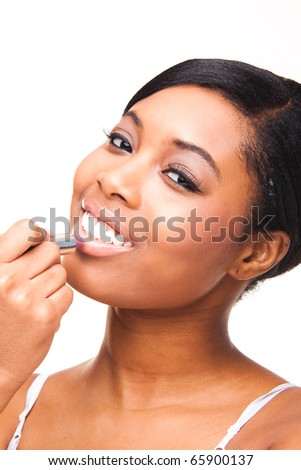 Portrait of a beautiful african black woman getting ready applying lipstick - stock photo
