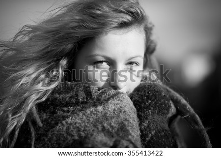 Portrait of a beautiful alternative young blonde girl with dreadlocks and a heavy scarf and a cityscape background