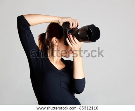 Portrait of a beautiful and attractive young woman holding a camera - stock photo