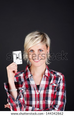 Portrait of a beautiful and confident young woman showing ace of hearts against black background - stock photo
