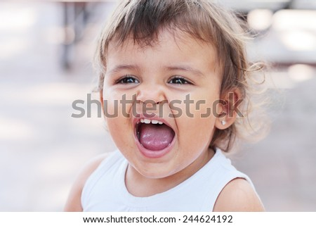 portrait of a beautiful and dirty screaming baby - stock photo