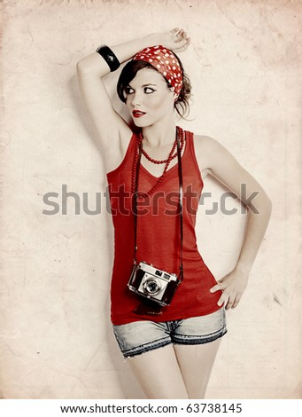 Portrait of a beautiful and fashion young woman with a photographic camera - stock photo