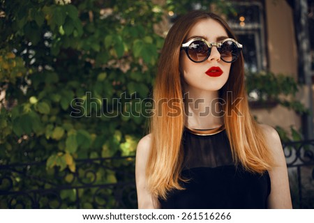 Portrait of a beautiful and fashionable girl in sunglasses with a gold rim. Posing in the park with professional hair style and make up. Blond hair with ombre coloring - stock photo
