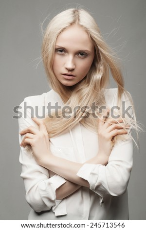 Portrait of a beautiful and gentle girl blonde with long hair in a studio on a gray background, the concept of health and beauty - stock photo
