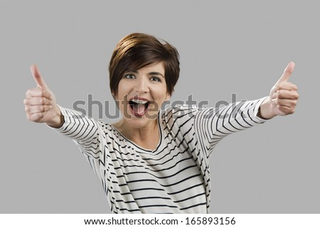 Portrait of a beautiful and happy woman with thumbs up, over a gray background - stock photo