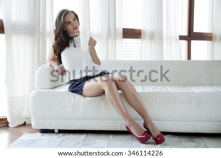 Portrait of a beautiful and sexy young adult attractive sensuality pretty brunette woman wearing elegance fashionable dress sitting in white sofa drinking coffee - stock photo