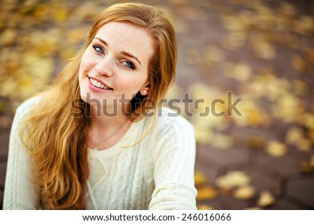 portrait of a beautiful and smiling redhead girl with freckles on the autumn landscape - stock photo
