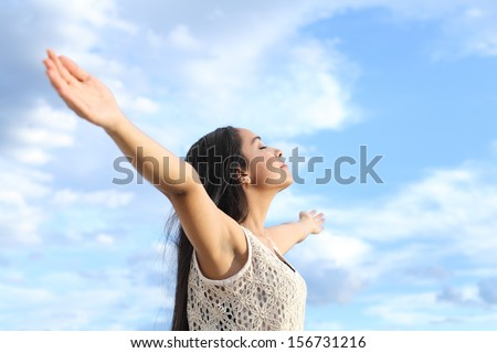 Portrait of a beautiful arab woman breathing fresh air with raised arms with a cloudy blue sky in the background          - stock photo