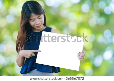 Portrait of a Beautiful asia woman holding a blank signboard with nature background. - stock photo