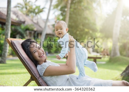 portrait of a beautiful asian mother having fun with his baby on a sunny day - stock photo