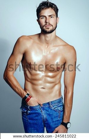 Portrait of a beautiful athletic men in jeans, studio photo - stock photo
