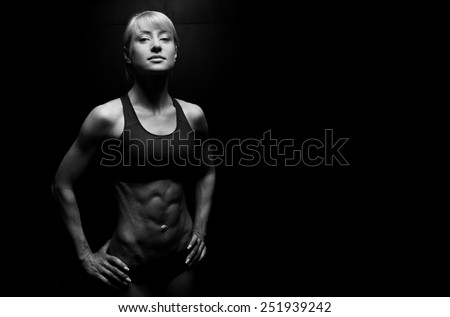 Portrait of a beautiful athletic woman on dark background - stock photo