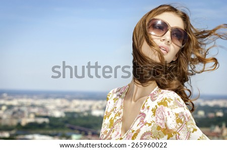 portrait of a beautiful attractive and sensuality young adult pretty brunette woman in sunglasses on background blue sunlight sky - stock photo