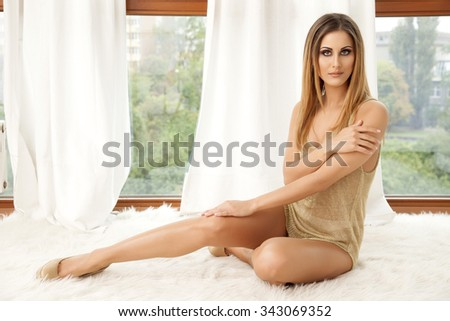 Portrait of a beautiful attractive and sexy young adult sensuality pretty brunette woman in gold blouse lying on the white fur - stock photo