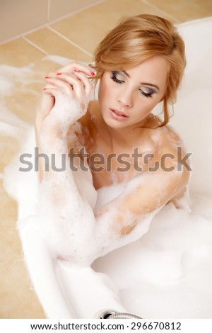 Portrait of a beautiful attractive sexy and sensuality young adult pretty blonde woman in bath relaxing. Closeup of young woman in bathtub bathing - stock photo