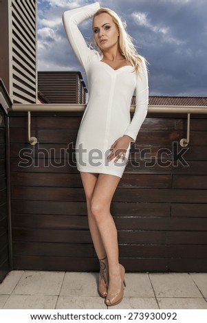 Portrait of a beautiful attractive slim sexy and sensuality young adult blonde woman in elegance white dress on the morning sunlight balcony - stock photo