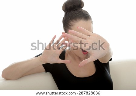 Portrait Of A Beautiful Attractive Young Caucasian Woman Posing On A Sofa Or Couch Fending Off Looking Scared anf Frightened Holding Hand Up In Defence - stock photo