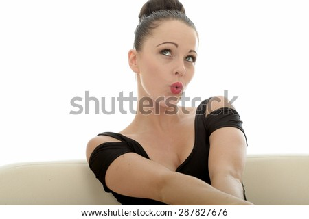 Portrait Of A Beautiful Attractive Young Caucasian Woman Relaxing And Posing On A Sofa Or Couch Whistling Looking Innocent and Guilty - stock photo