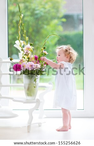 Portrait of a beautiful baby girl playing with fresh flowers wearing a white dress standing next to a window and door to the garden - stock photo