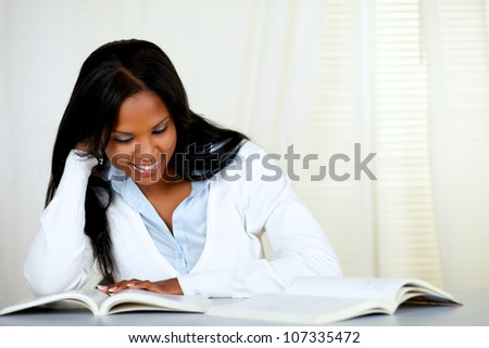 Portrait of a beautiful black woman smiling and reading a book at home indoor - stock photo