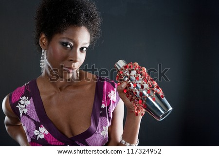 Portrait of a beautiful black young woman mixing a cocktail with a cocktail shaker in a dark background. - stock photo