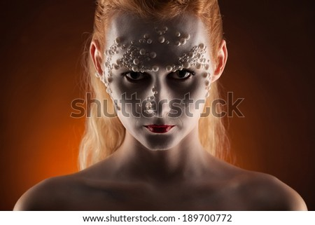 portrait of a beautiful blond girl vampire with bloody streaks  - stock photo