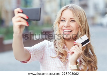 Portrait of a beautiful blond girl with long wavy hair wearing pink dress, holding a credit card smiling and making a selfie on her smartphone