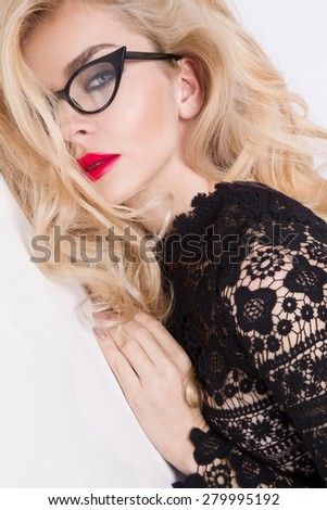 Portrait of a beautiful blond woman very with green eyes of sweet red lips in a sensual hairstyle with a sexy look with glasses - stock photo