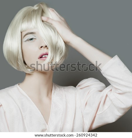 Portrait of a beautiful blond woman with short hair in studio on gray background - stock photo