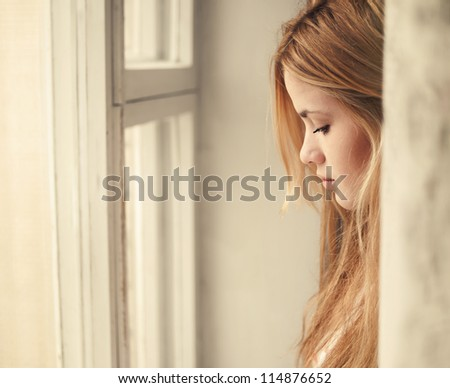portrait of a beautiful blonde at the window - stock photo