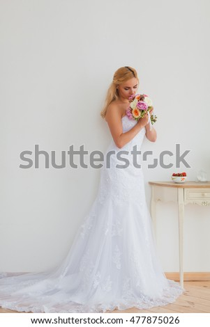Portrait of a beautiful blonde bride with bouquet, wedding concept