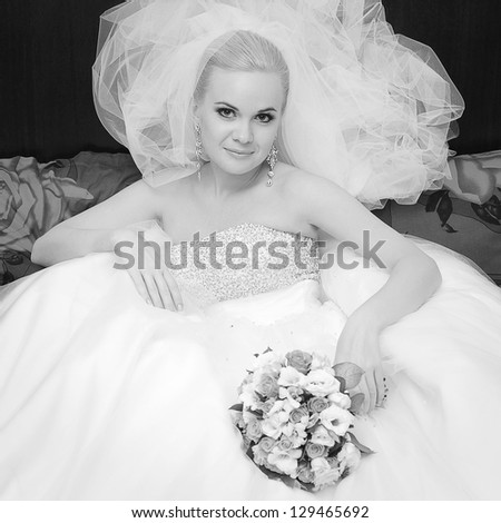 Portrait of a beautiful blonde bride with great vapory veil and wedding bouquet. Indoor black and white shot - stock photo