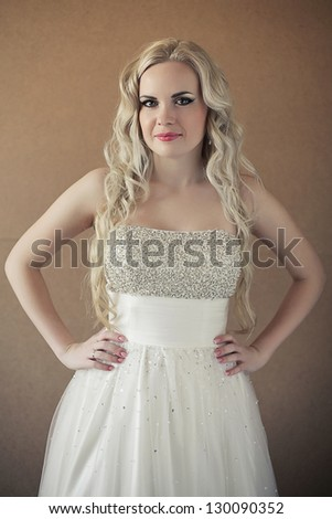 Portrait of a beautiful blonde bride with long curly hair posing over wooden background. daylight. studio shot - stock photo
