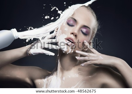 Portrait of a beautiful blonde dousing with cream - stock photo