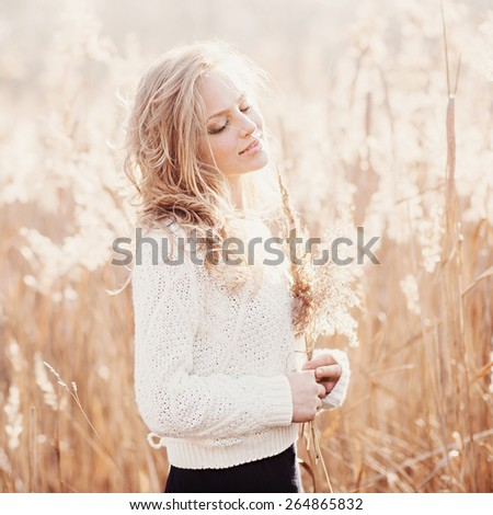 Portrait of a beautiful blonde girl in a field in white pullover, smiling with eyes closed, concept beauty and health - stock photo