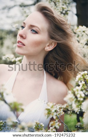 portrait of a beautiful blonde girl in the flowered garden