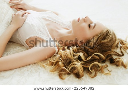 Portrait of a beautiful blonde girl lying on a white bed - stock photo
