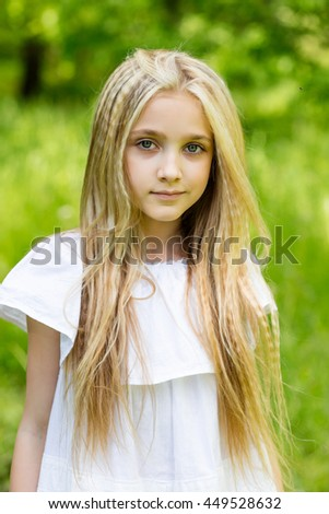 Portrait of a beautiful blonde girl outdoors in summer