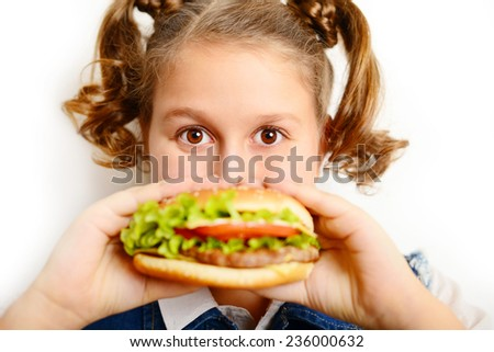 portrait of a beautiful blonde girl, teenager and schoolgirl, holding a hamburger on a white background - stock photo