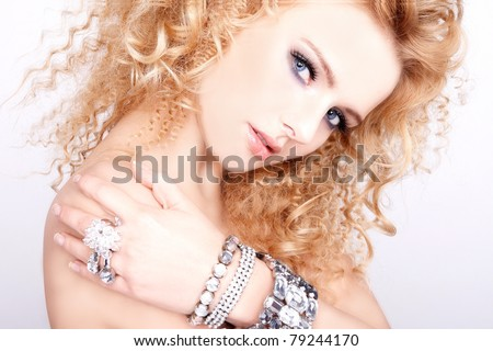 portrait of a beautiful blonde girl with luxury accessories isolated on white background - stock photo