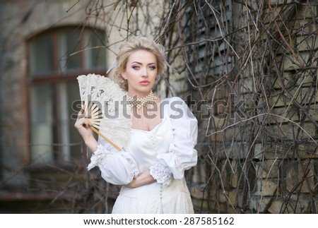 Portrait of a beautiful blonde in an old white dress with a fan in a pearl necklace, beautiful color, toning unusual, mysterious atmosphere, mystic - stock photo