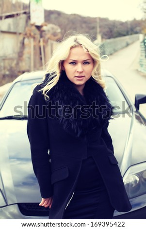 portrait of a beautiful blonde woman driving a sports car - stock photo