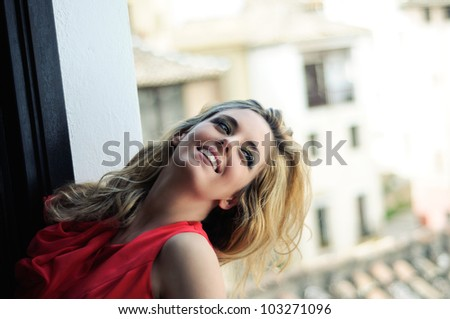 Portrait of a beautiful blonde woman in a window wearing a red dress - stock photo
