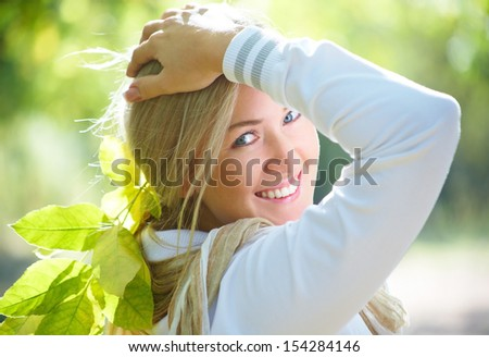 Portrait of a beautiful blonde woman in autumn park - stock photo