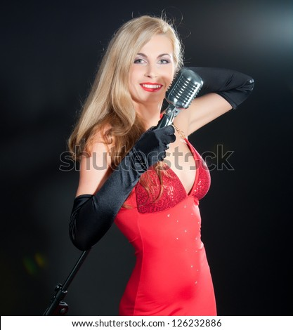 Portrait of a beautiful blonde woman in red dress and black gloves with a retro microphone.